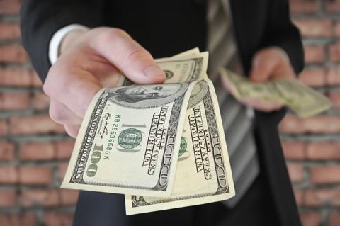 A man in a business suit offers money (copyright by Shutterstock/Oleksandrum)