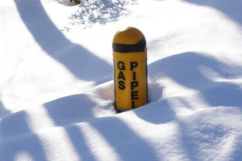 Marker for natural gas pipeline partly buried in snow after winter storm (copyright by Shutterstock/Imageforge)