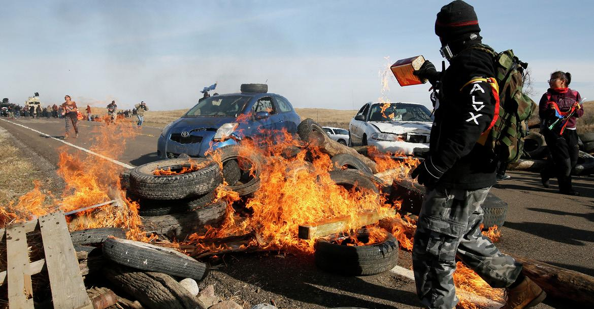 A protester pours gasoline on a fire blocking North Dakota Highway 1806 on Oct. 27, 2016, north of Cannon Ball. Protesters of the Dakota Access Pipeline were attempting to keep law enforcement officers from pushing them off the road and out of their camp. (copyright by INFORUM)