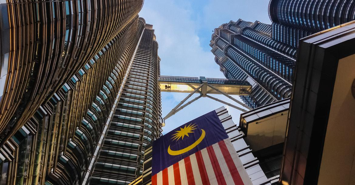 Petronas Towers with Malaysia national flag (copyright by Shutterstock/sacitarios)